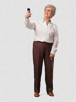Full body senior woman fiducioso e allegro, prendendo un selfie, guardando il cellulare con un gesto divertente e spensierato, navigando i social network e internet