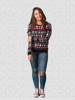 Full body giovane donna che indossa una maglia di natale allegro con un grande sorriso