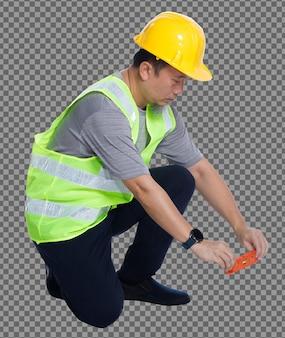 L'intera lunghezza degli anni '50 e '60 dell'uomo anziano asiatico ingegnere indossa gli strumenti del casco del giubbotto di sicurezza, livello di equilibrio. vista lato posteriore posteriore maschio anziano seduto e linea di equilibrio con attrezzatura livella a bolla su bianco isolato
