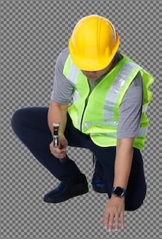 Figura intera degli anni '50 e '60 uomo anziano asiatico ingegnere costruttore indossare giubbotto di sicurezza elmetto rigido martello. il maschio anziano si siede e colpisce il chiodo con il martello su sfondo bianco isolato