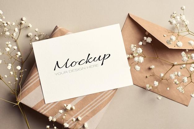 Biglietto di auguri o modello di invito con busta, confezione regalo e fiori di hypsophila bianchi