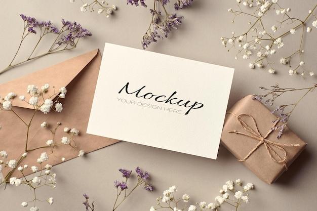Mockup stazionario per biglietti di auguri con busta, confezione regalo e decorazioni di fiori secchi