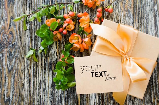 Confezione regalo con fiocco fiocco, etichetta vuota e ramo fiorito delicato.