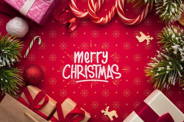 Contenitori di regalo e bastoncini di zucchero sul fondo di rosso di natale
