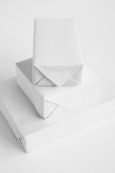 Mockup di scatole regalo su un tavolo in carta da imballaggio minimalista pulita