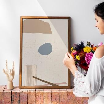 Ragazza che decora una parete con una cornice