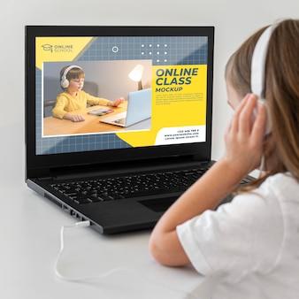 Ragazza con le cuffie utilizzando laptop