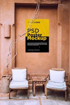 Mockup di poster incollato e sgualcito sul vecchio muro di grunge con sedie in legno