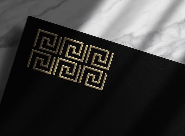 Mockup di carta nera goffrata oro con sfondo marmer dall'alto