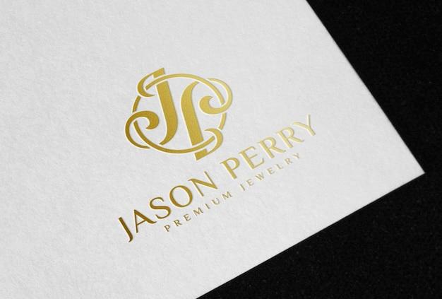 Logo in lamina d'oro su cartoncino bianco