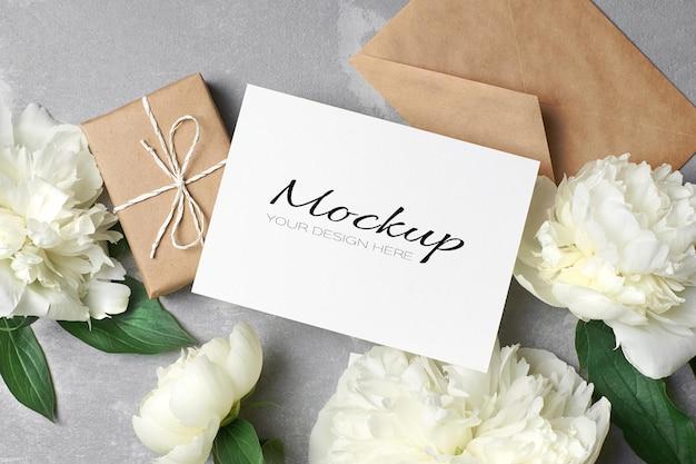 Modello di biglietto di auguri o invito con busta, confezione regalo e fiori di peonia bianca su grigio