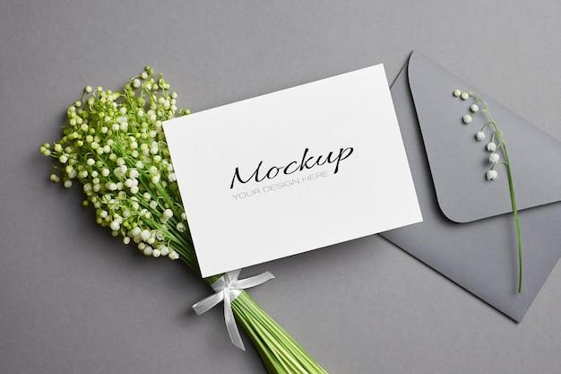 Modello di biglietto di auguri o invito con busta e bouquet di fiori di mughetto