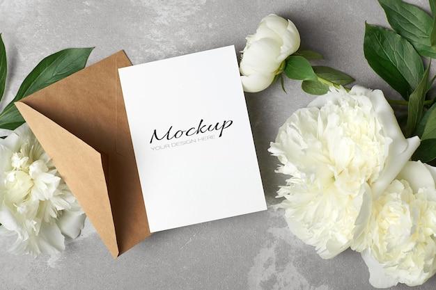 Modello di biglietto di auguri o invito con busta e fiori di peonia bianca su grigio