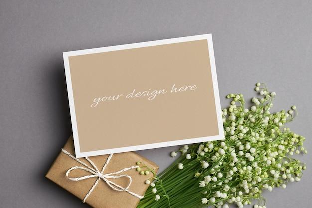 Modello di biglietto di auguri o invito con scatola ift e bouquet di fiori di mughetto