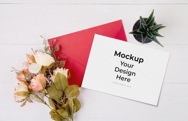 Biglietto di auguri mockup e fiore sulla tavola di legno