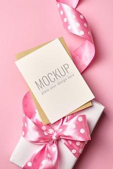 Mockup di biglietto di auguri con grande confezione regalo con fiocco