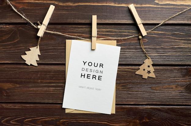 Mockup di biglietto di auguri con decorazioni natalizie sul tavolo di legno scuro