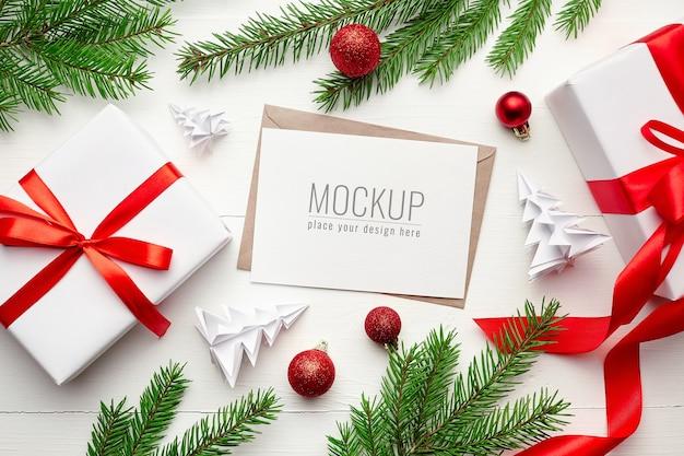 Mockup di biglietto di auguri con decorazioni natalizie e rami di abete