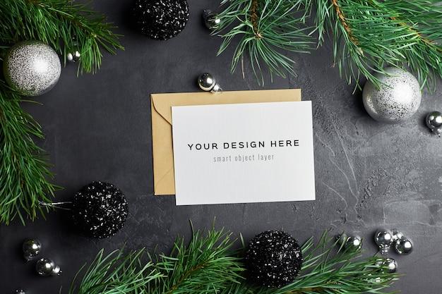 Mockup di biglietto di auguri con decorazioni natalizie e rami di pino su oscurità