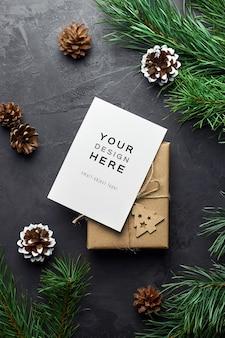 Mockup di biglietto di auguri con scatola regalo di natale e rami di pino e coni