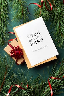 Mockup di biglietto di auguri con scatola regalo di natale e rami di pino sul verde