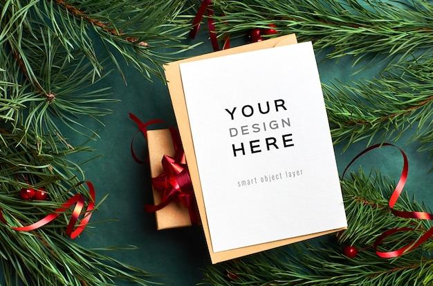 Mockup di biglietto di auguri con scatola regalo di natale e rami di pino con nastro rosso sul verde