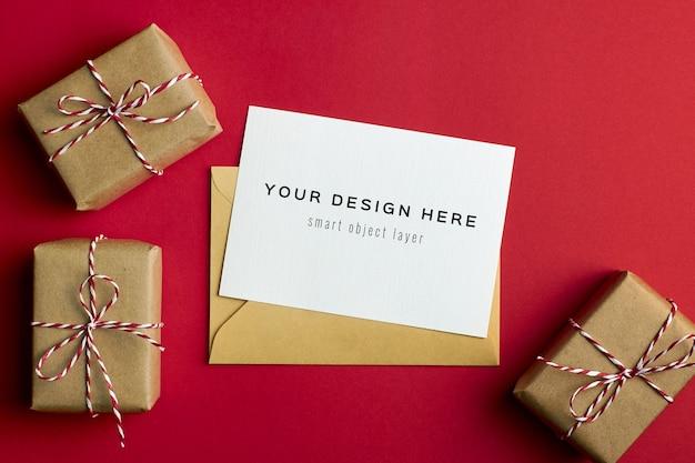 Mockup di biglietto di auguri con scatole regalo di natale su sfondo di carta rossa