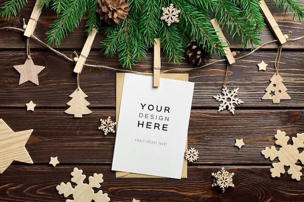 Mockup di biglietto di auguri con decorazioni natalizie in legno e rami di abete