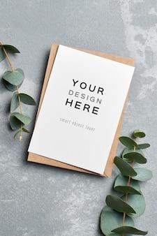 Mockup di biglietto di auguri con busta e ramoscelli di eucalipto su grigio