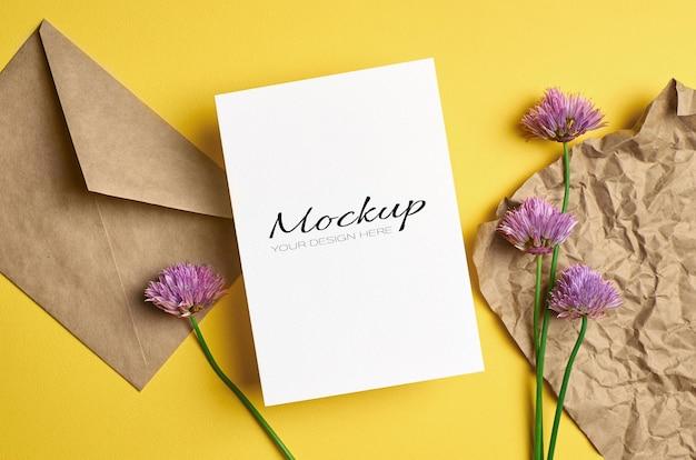 Modello di biglietto di auguri con busta e fiori su giallo
