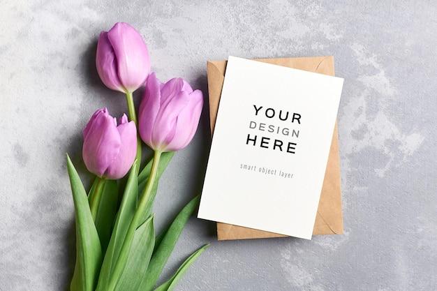 Mockup di biglietto di auguri con busta e fiori freschi di tulipano su grigio