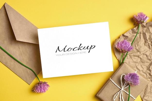 Modello di biglietto di auguri con busta, confezione regalo e fiori su giallo