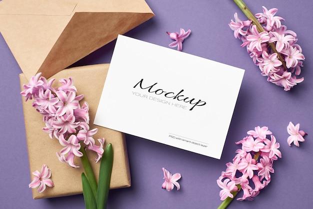 Mockup di biglietto di auguri con busta, confezione regalo e fiori di giacinto rosa