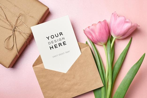 Mockup di biglietto di auguri con busta, confezione regalo e fiori di tulipano rosa