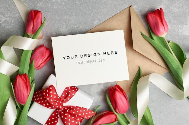 Mockup di biglietto di auguri con busta, confezione regalo e fiori di tulipano rosso