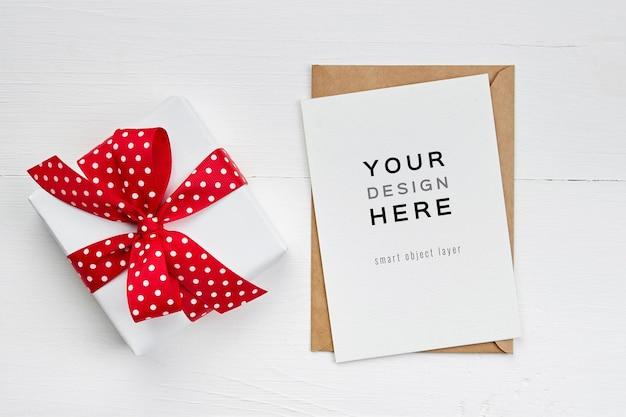 Mockup di biglietto di auguri con busta e confezione regalo con nastro rosso su bianco