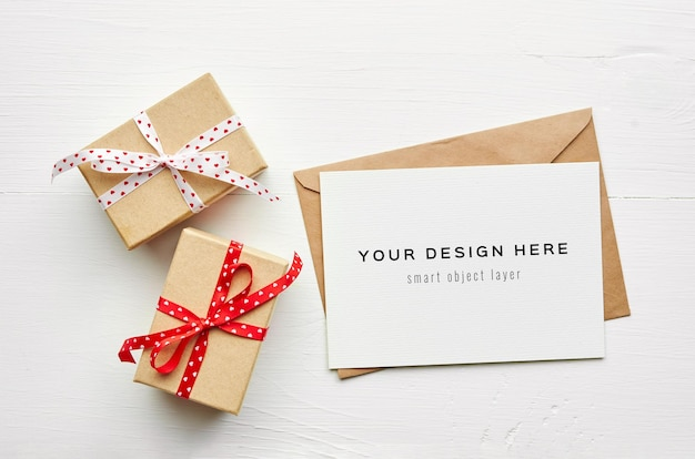 Mockup di biglietto di auguri con busta e scatole regalo su sfondo bianco