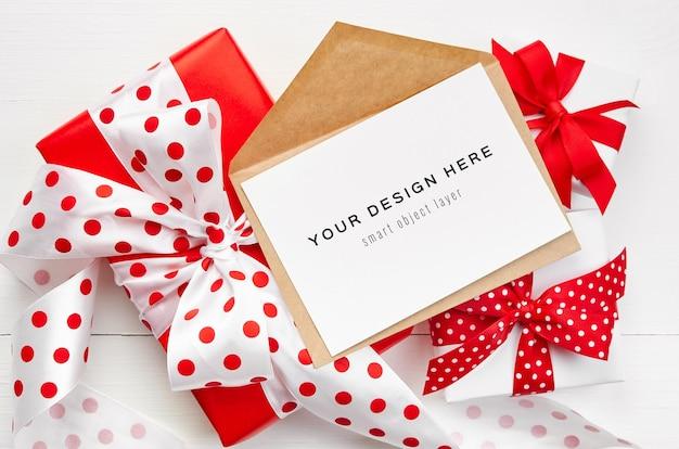 Mockup di biglietto di auguri con busta e scatole regalo con nastri rossi