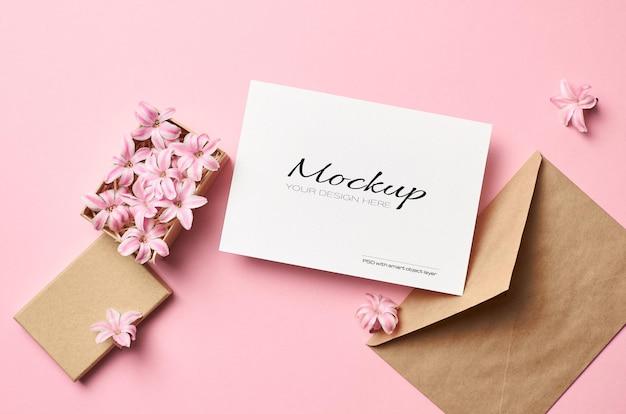 Mockup di biglietto di auguri con busta e fiori rosa in scatola