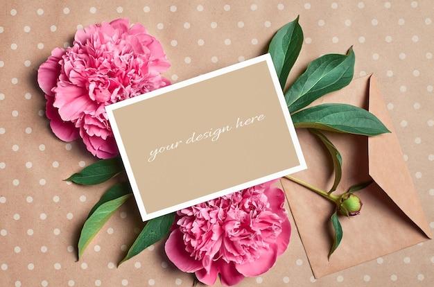 Modello di biglietto di auguri con busta e fiori di peonia rosa su sfondo di carta artigianale