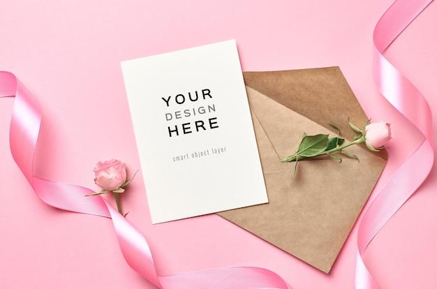 Mockup di biglietto di auguri con busta, nastro rosa e fiore di rosa