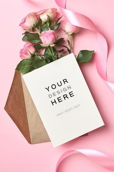 Mockup di biglietto di auguri con busta, nastro rosa e bouquet di fiori di rose