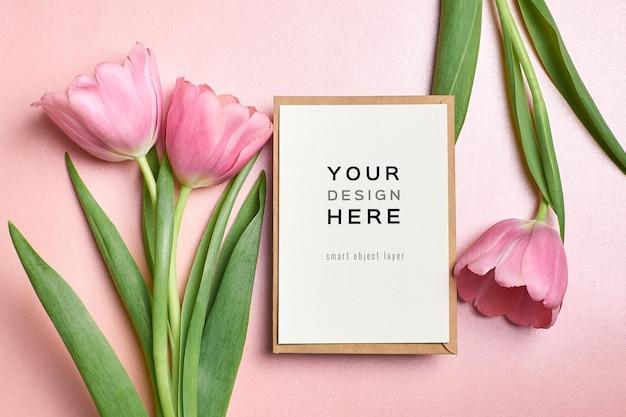 Mockup di biglietto di auguri con busta e fiori di tulipano rosa