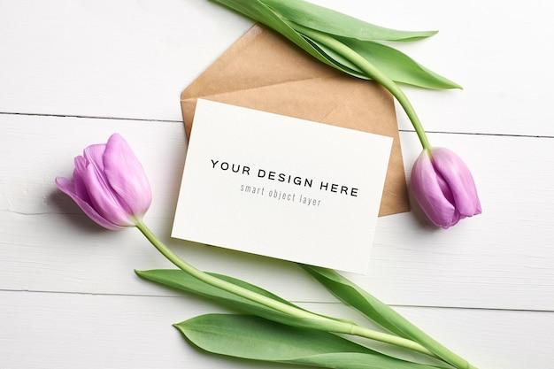 Mockup di biglietto di auguri con busta e fiori di tulipano viola sulla tavola di legno bianca