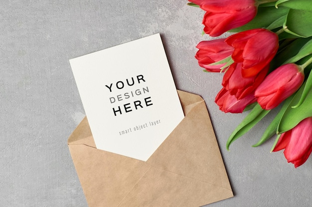 Mockup di biglietto di auguri con busta e bouquet di fiori di tulipano rosso