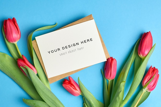 Mockup di biglietto di auguri con busta e fiori di tulipano rosso