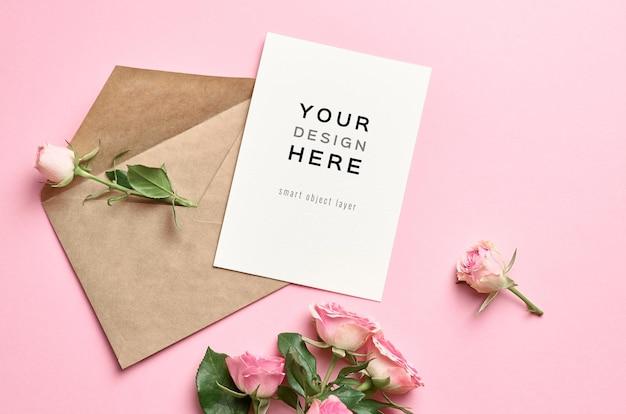 Mockup di biglietto di auguri con busta e bouquet di fiori di rose sul rosa