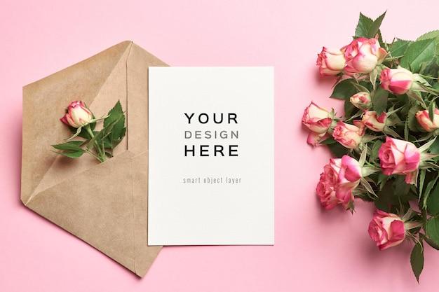 Mockup di biglietto di auguri con busta e fiori di rose su sfondo rosa