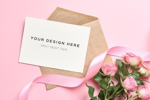 Mockup di biglietto di auguri con busta, fiori di rose e nastro rosa