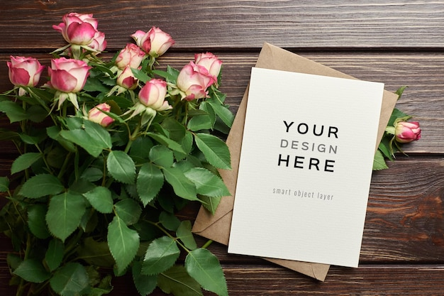 Mockup di biglietto di auguri con busta e fiori di rose su fondo in legno